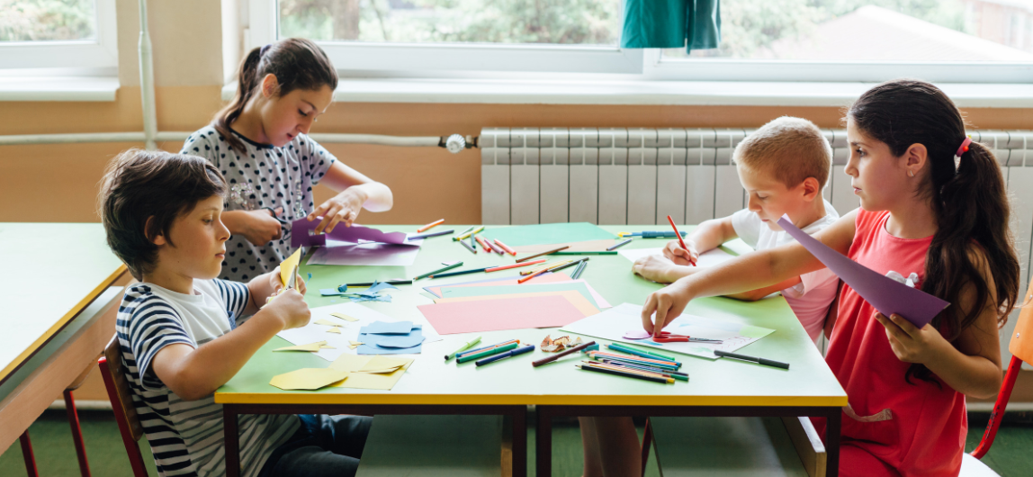 kids sitting at a school table with colorful paper activities