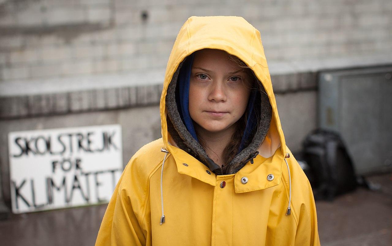 Portrait of Greta Thunberg in a yellow rain jacket with hood up