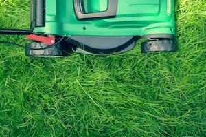 green lawnmower mowing green grass