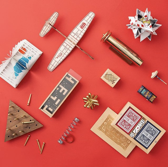 Toy airplane, games, and cards in front of a red background