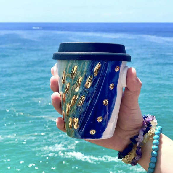 Blue, green, and gold to-go coffee mug in front of a blue ocean