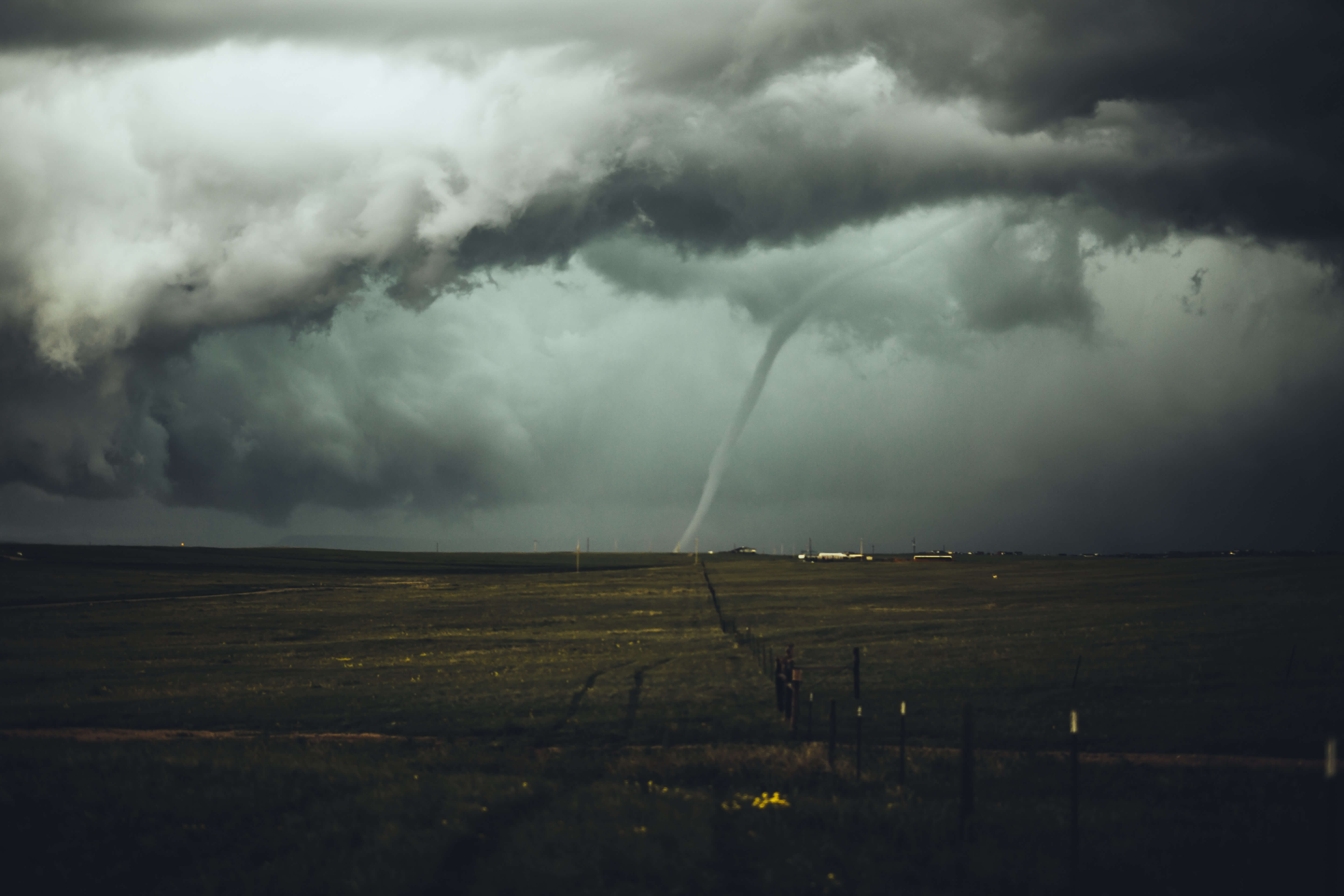 tornado at a distance in a green field