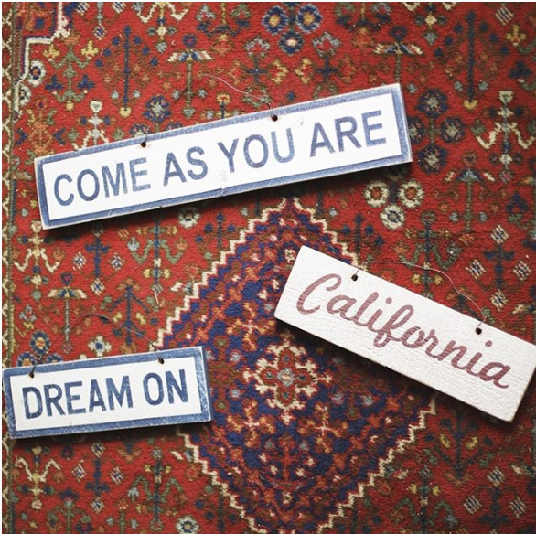 Signs that say come as you are, dream on, and California in front of a red background