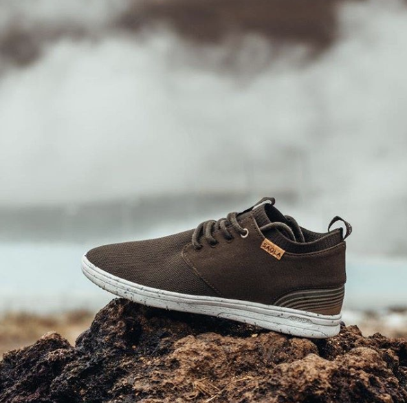 A brown shoe on a rock in front of the ocean