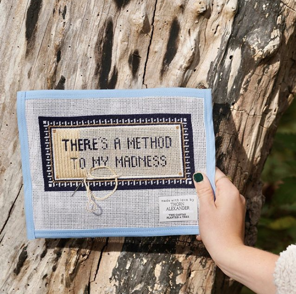 Blue needlepoint in front of a tree