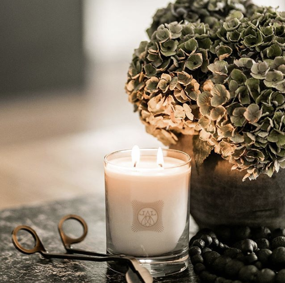 White burning candle next to green flowers