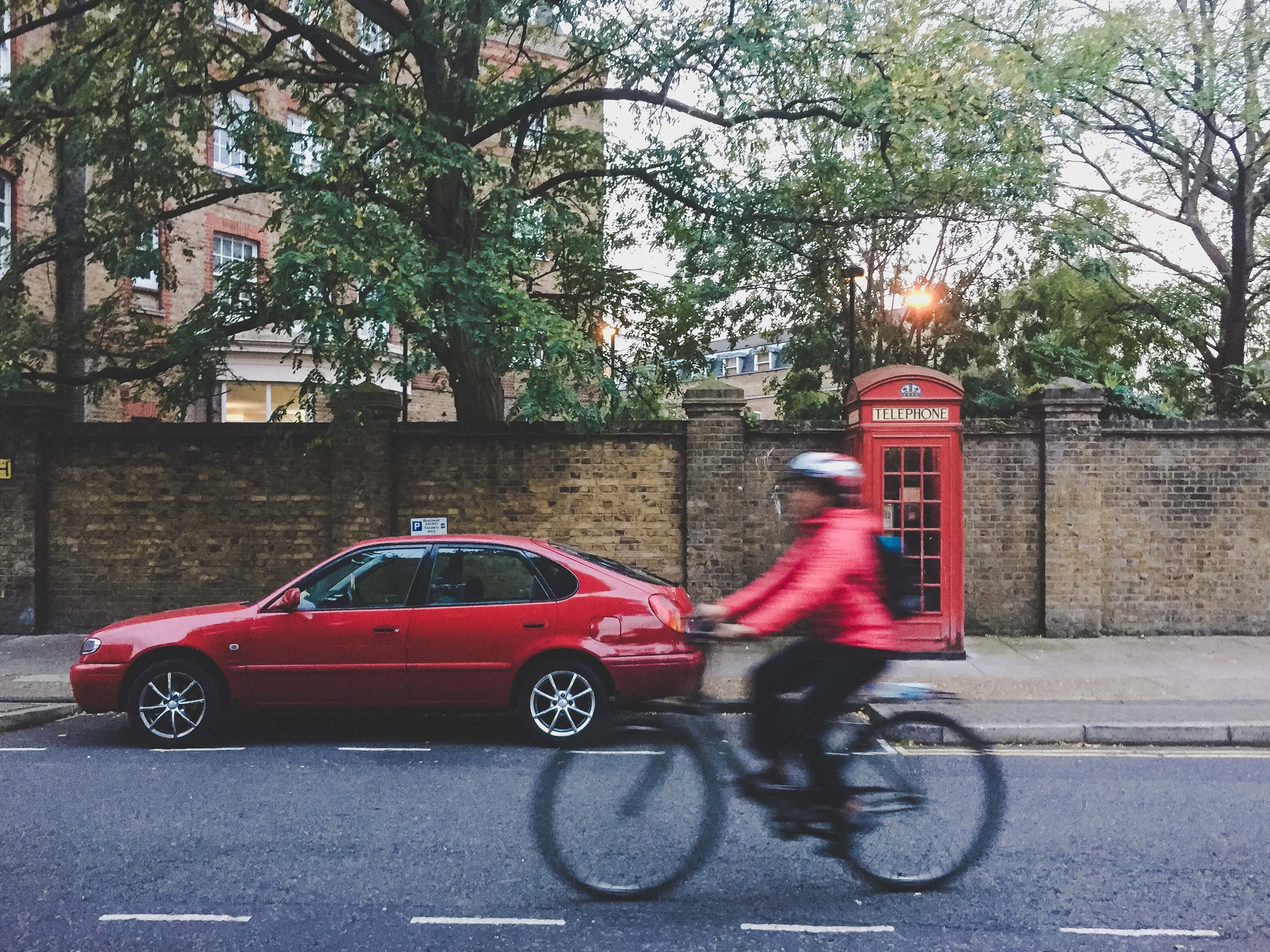 Trees, bike, car and red phone booth on London street