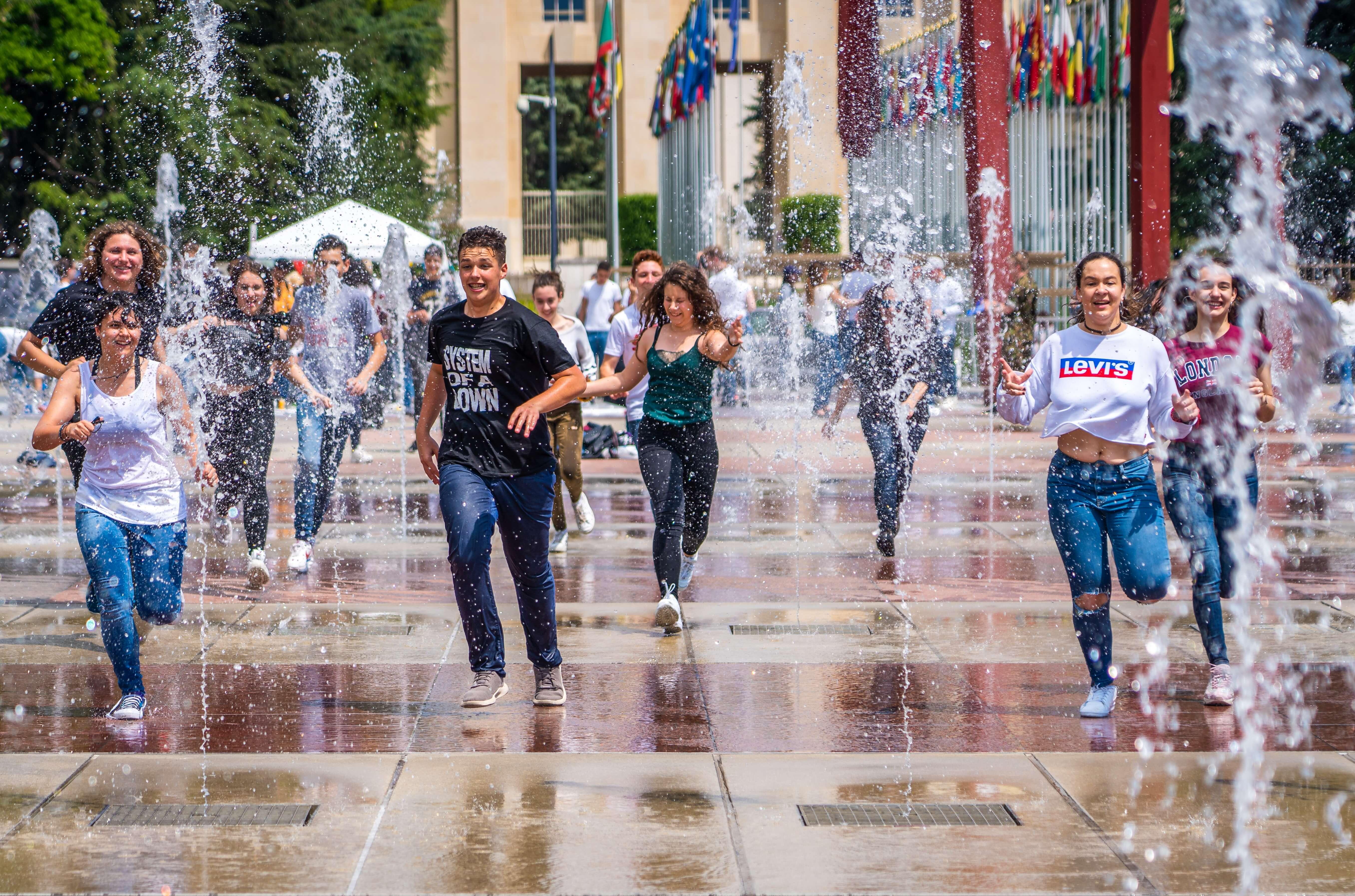 people splashing through water fountains