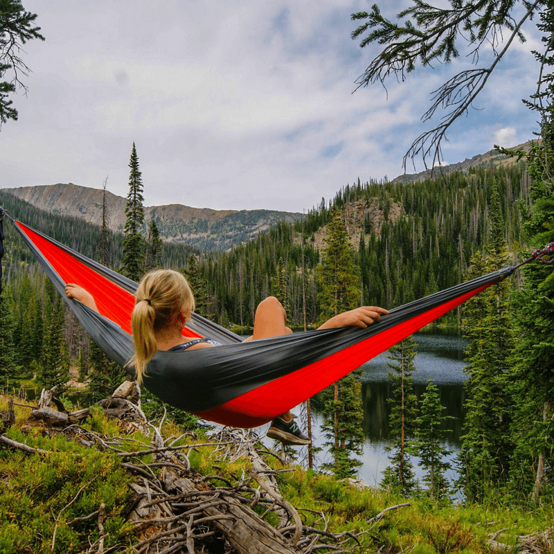 Woman laying in a hammock overlooking a forest and mountains