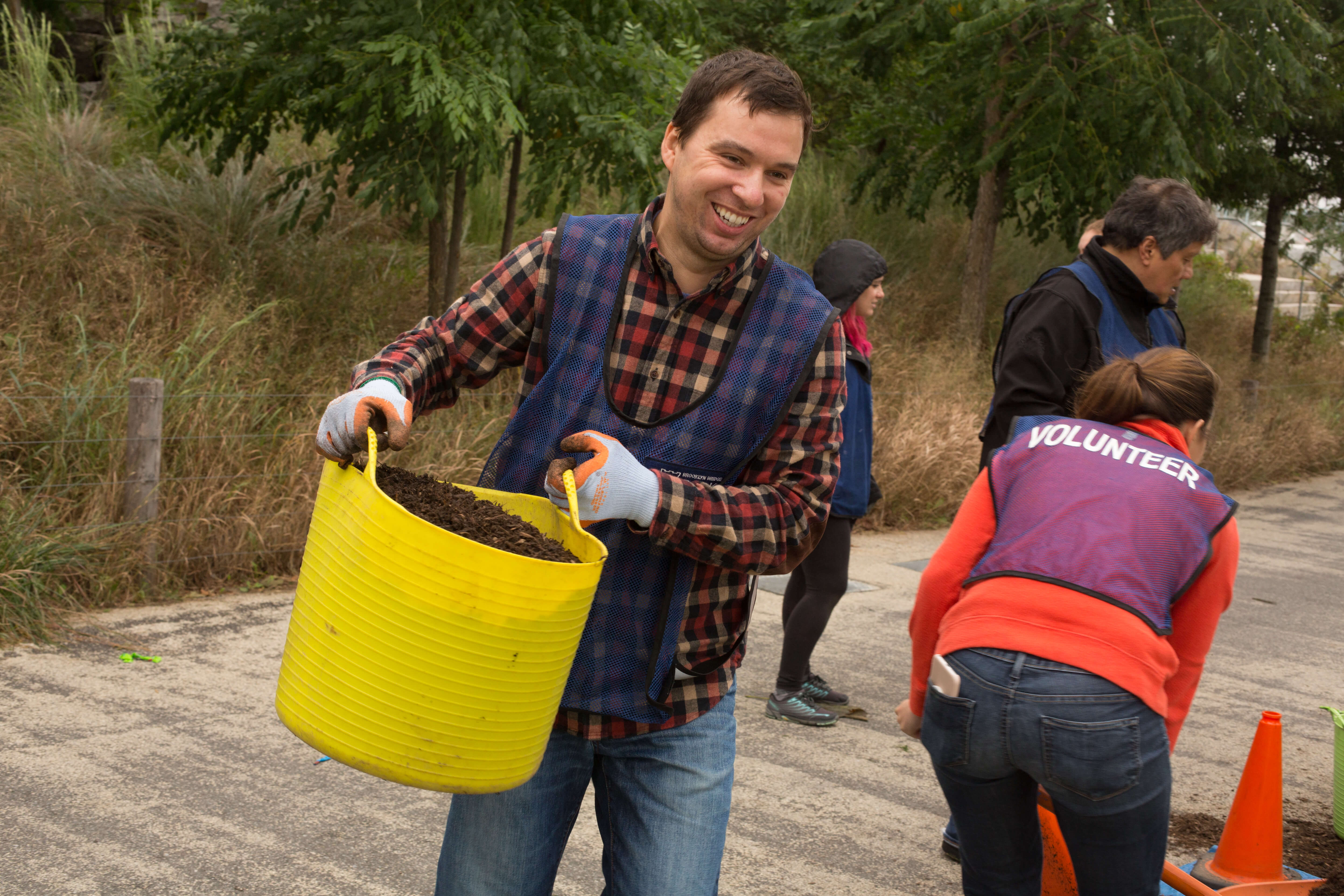 Man carrying bucket of mulch and smiling