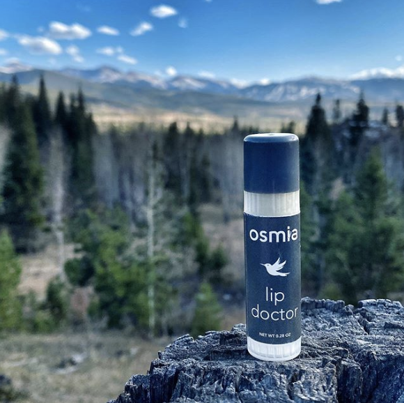 Osmia lip doctor bottle in front of mounts and pine trees
