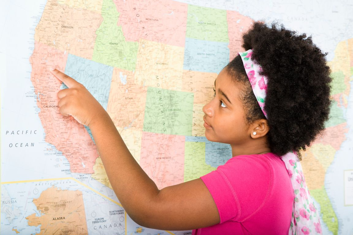girl in school with a pink top pointing at a map of the west coast of the United States