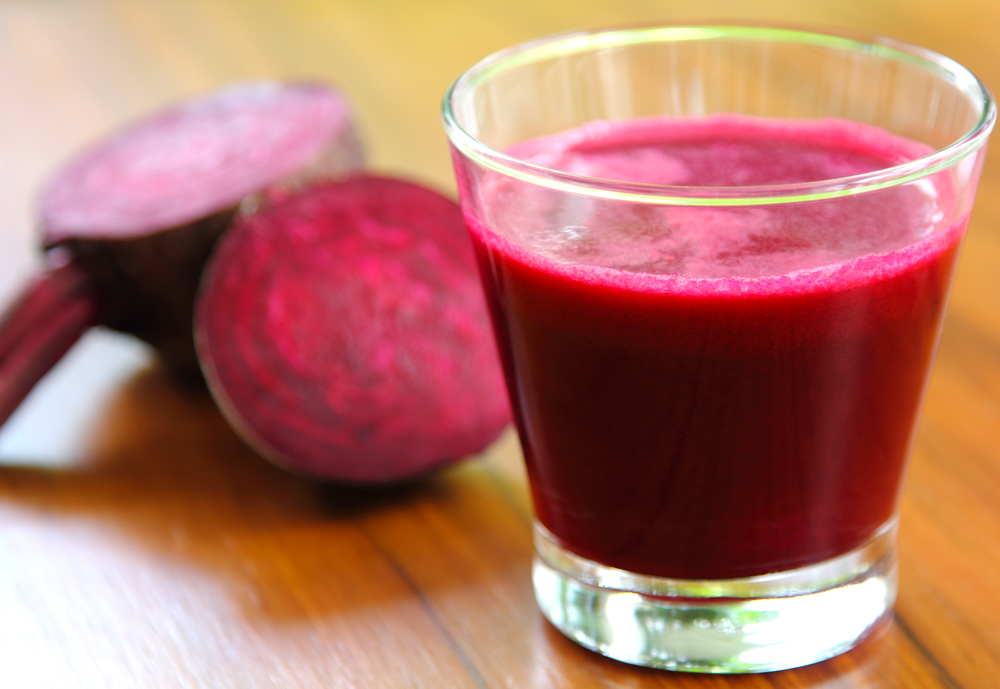 red beet juice in glass with beets behind it