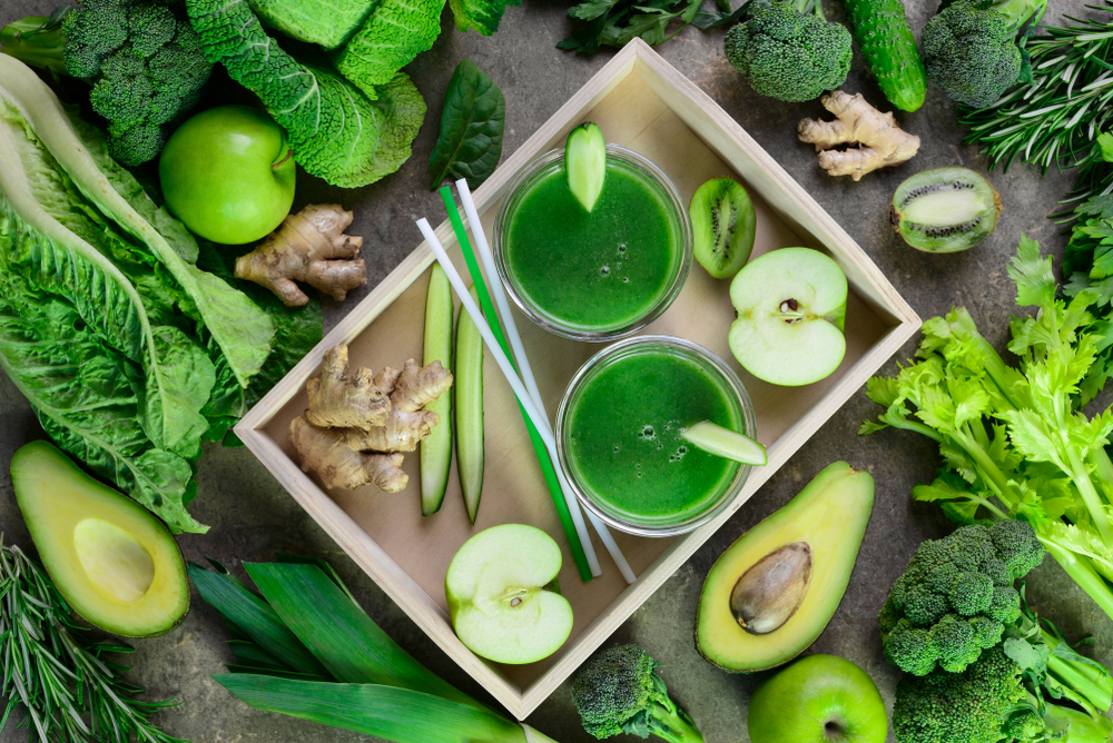 image of green juicer surrounded by green vegetables