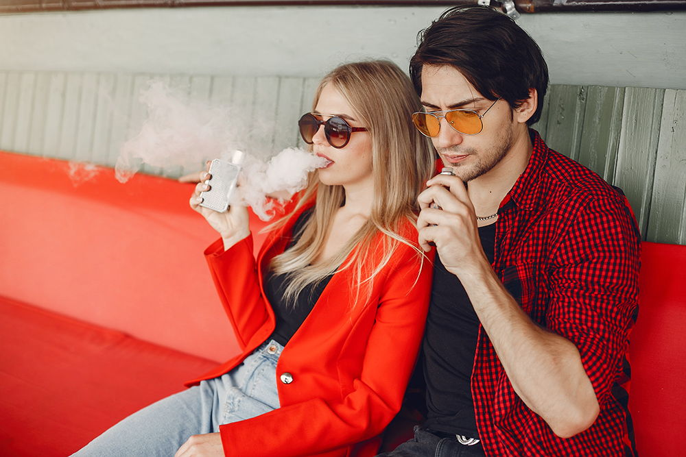 elegant couple relaxing and vaping