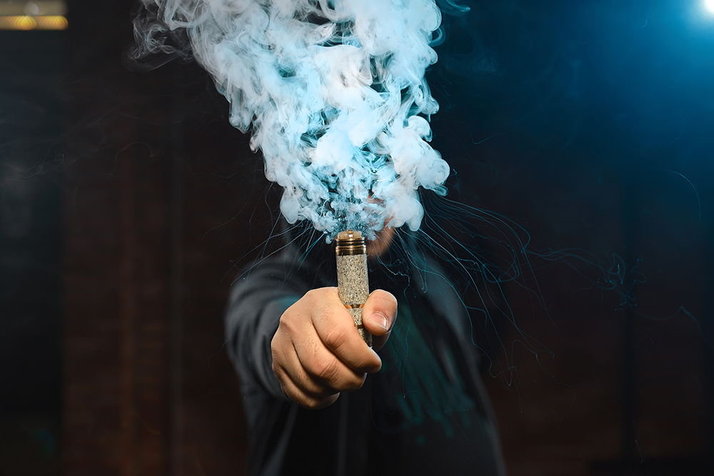 vaping device in left hand creating huge clouds