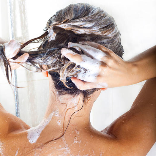 Woman massaging her head with Shampoo.