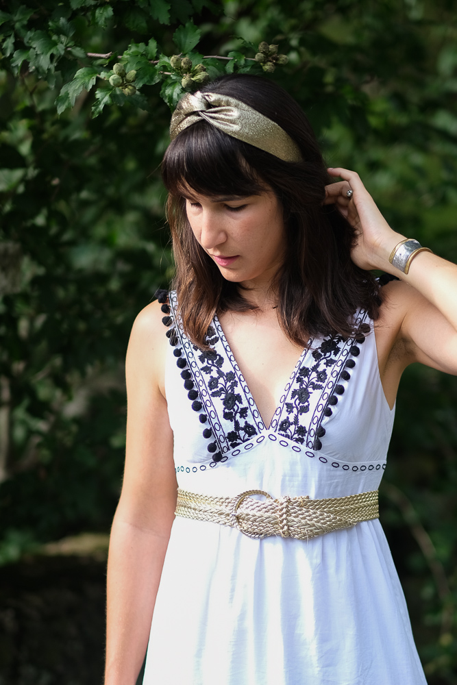 Woman in white dress and gold headband. Cleopatra Halloween costume.