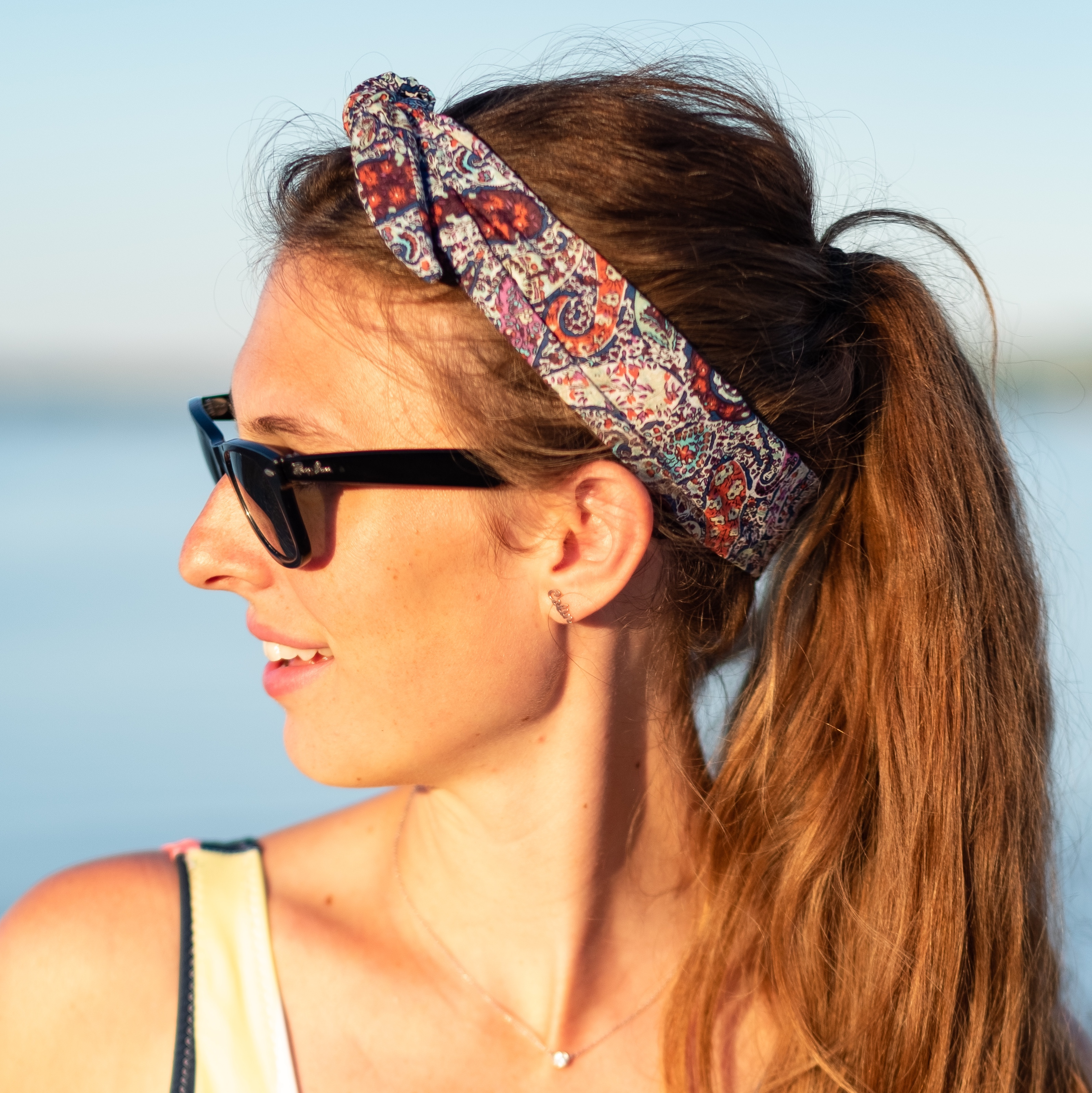Beautiful woman with long blonde ponytail, wearing wire-framed colorful paisley bandana.