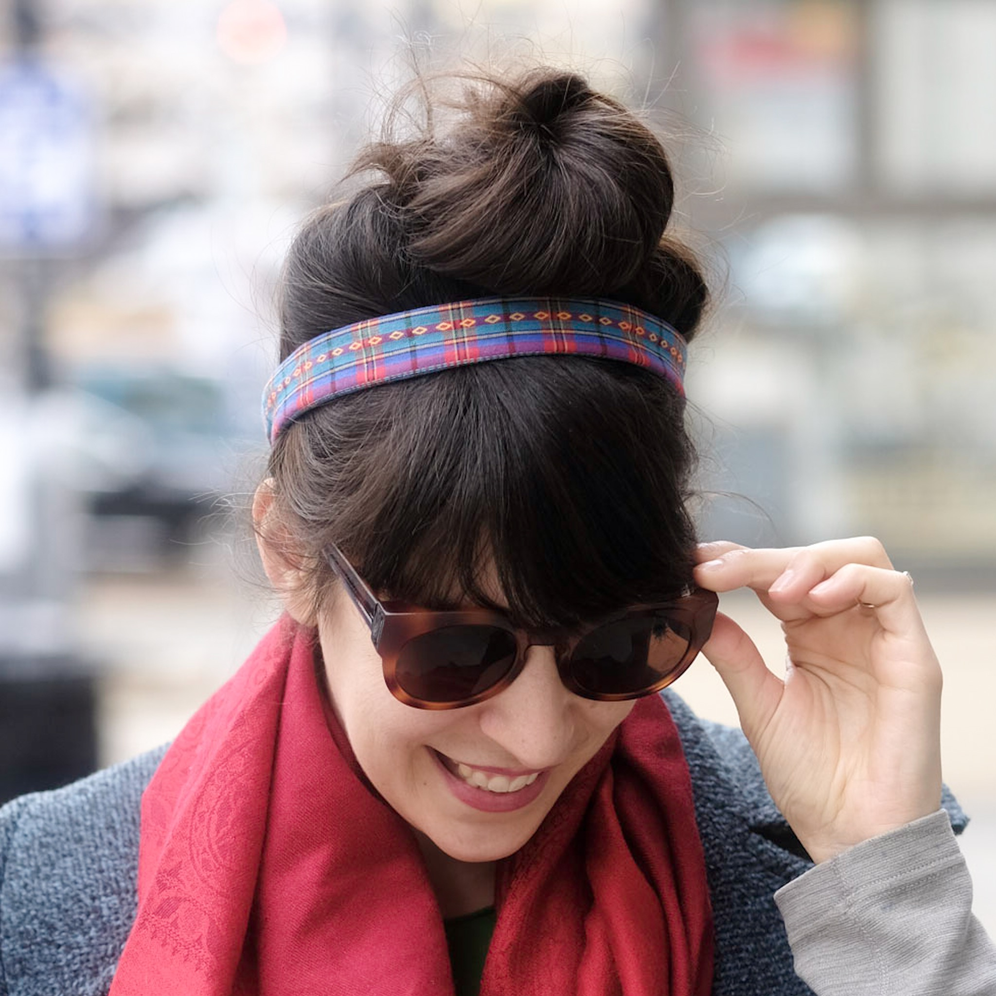 Beautiful woman smiling and looking down, while wearing a multicolor plaid wire-framed headband.