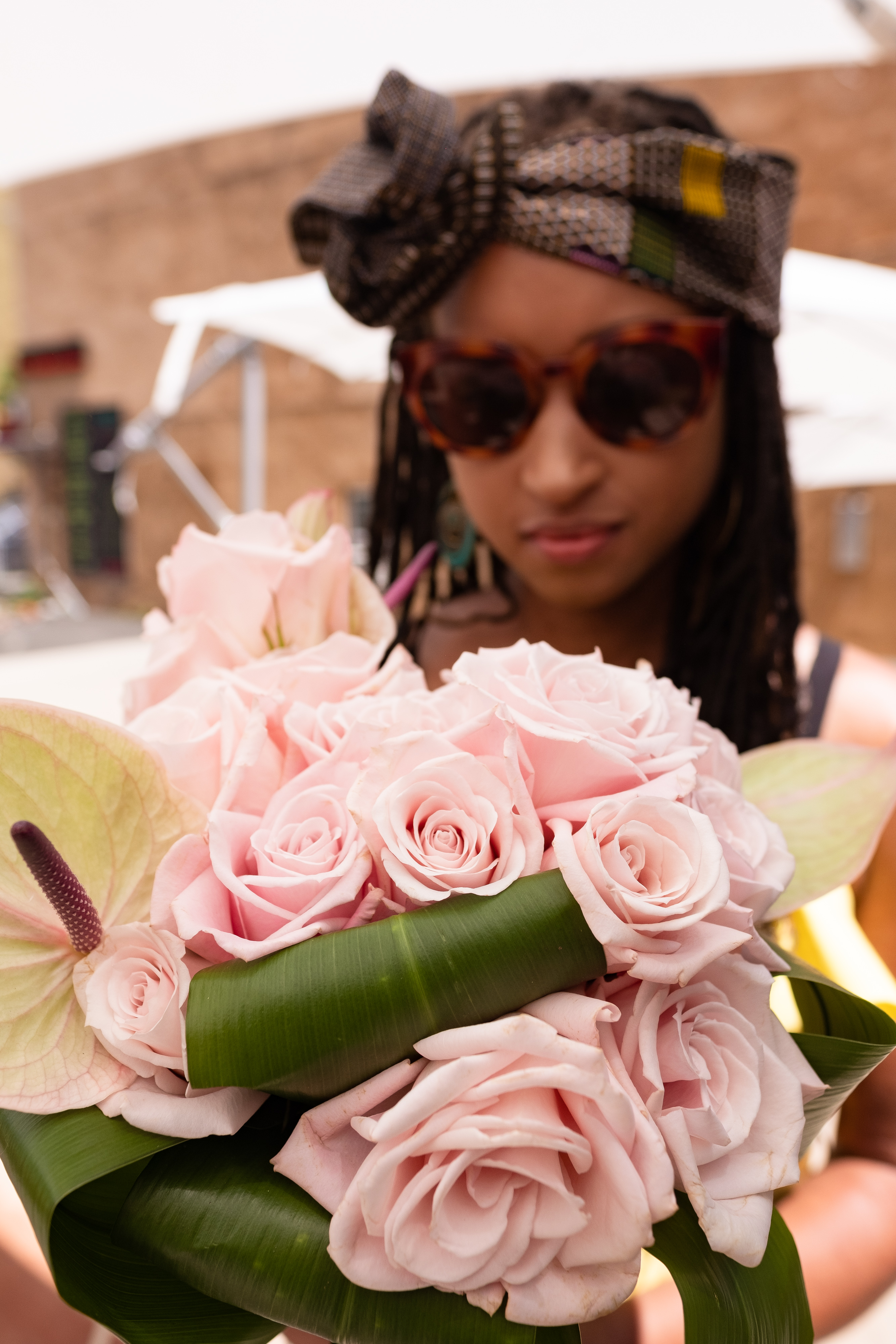 Beautiful woman wearing sunglasses and a brown headwrap with blocks of color throughout; pink roses in the foreground.