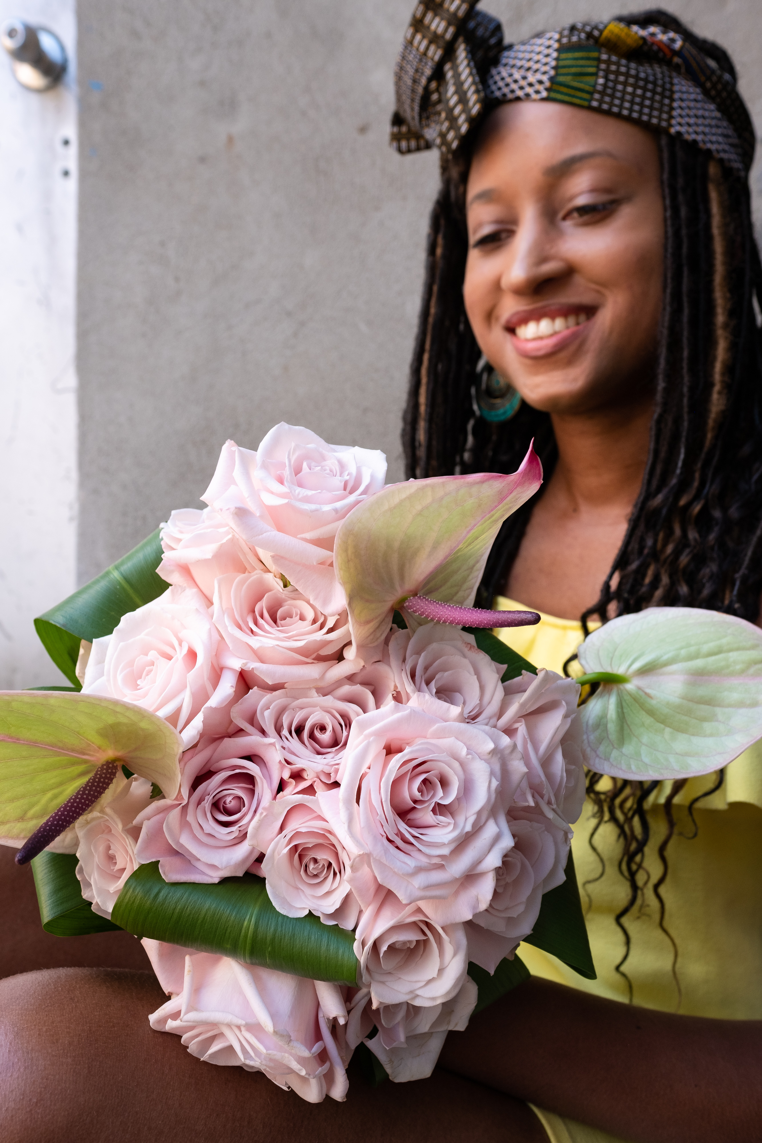 Beautiful, smiling woman wearing a brown headwrap with blocks of color throughout, looking down at beautiful pink roses.