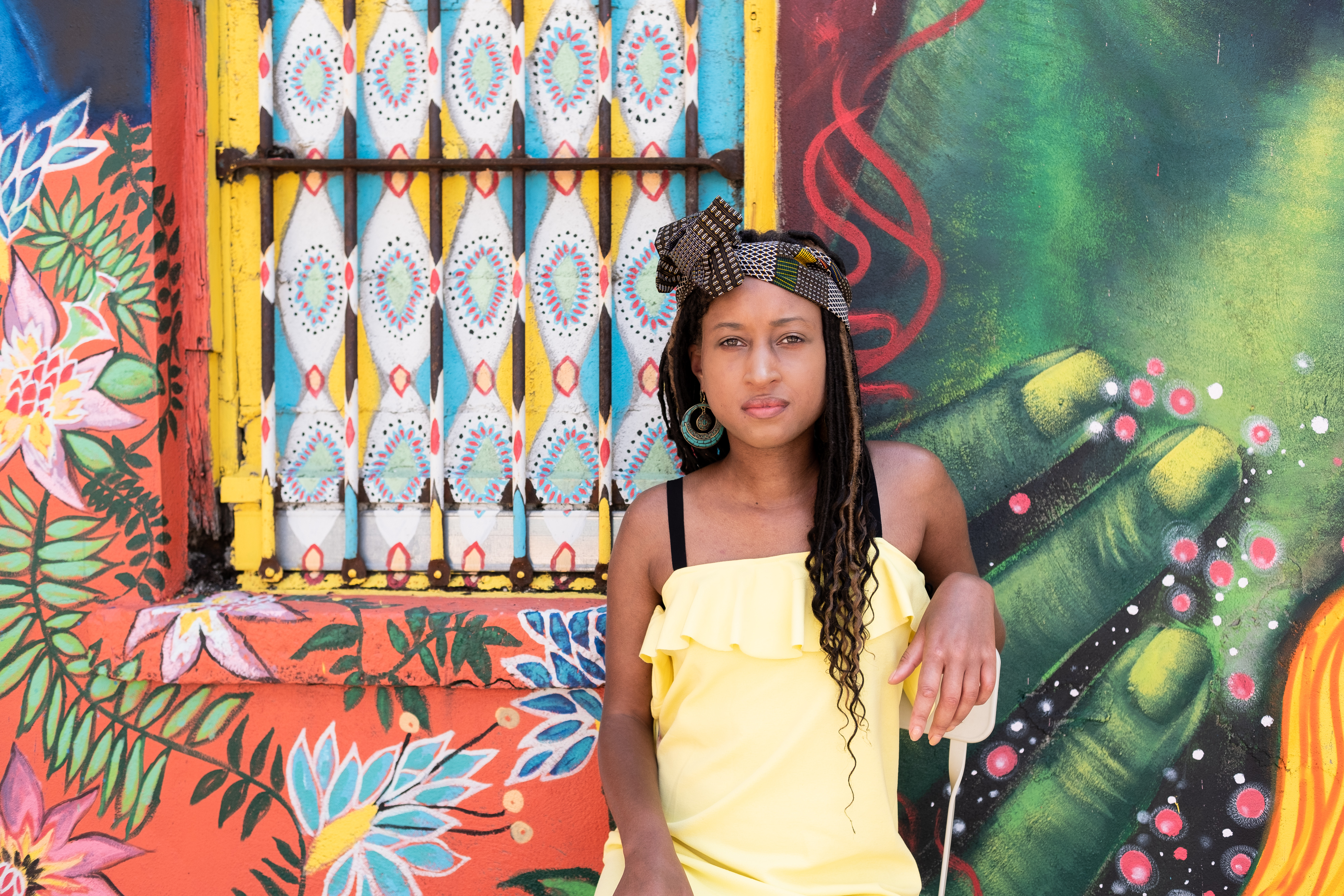 Beautiful woman wearing a brown headwrap with blocks of color throughout, against a colorful mural at Cassava House.