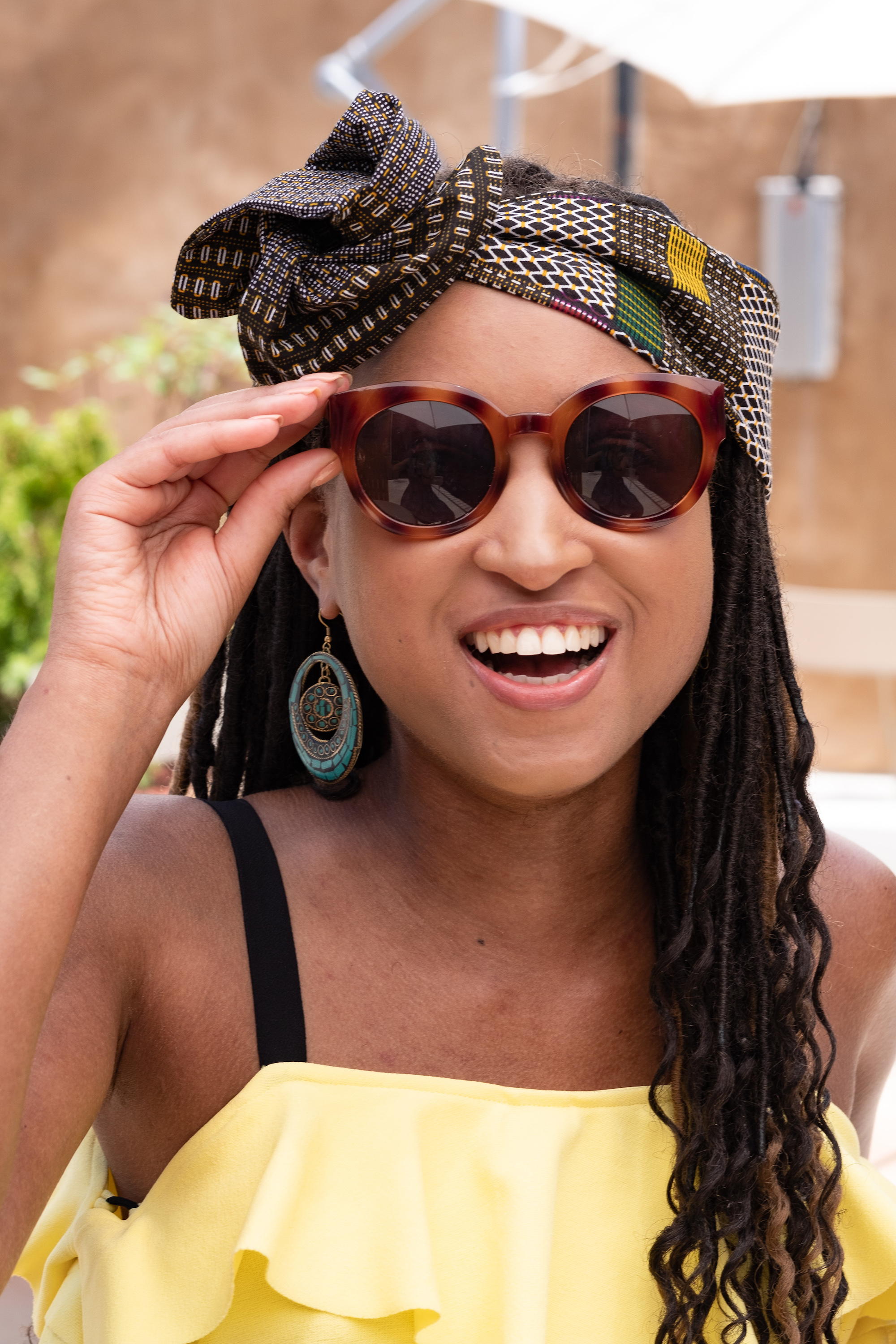 Smiling woman wearing sunglasses and a brown headwrap with blocks of color throughout.