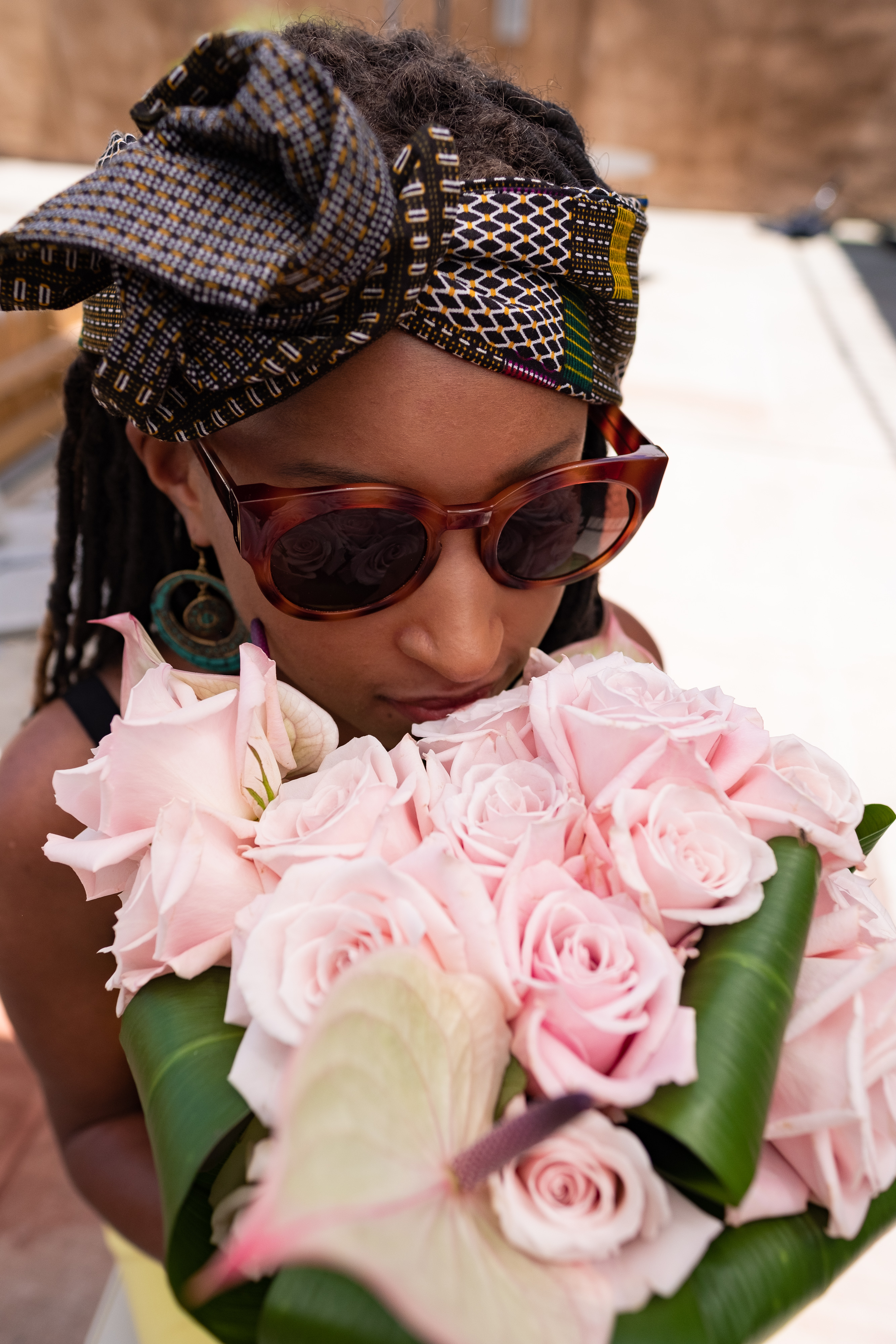 Beautiful woman wearing sunglasses and a brown headwrap with blocks of color throughout, smelling pink roses.