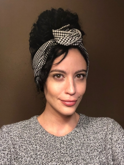 Woman wearing hair up in bun with wide gingham printed headband tied into a rosette for Mod/ Bardot Halloween look