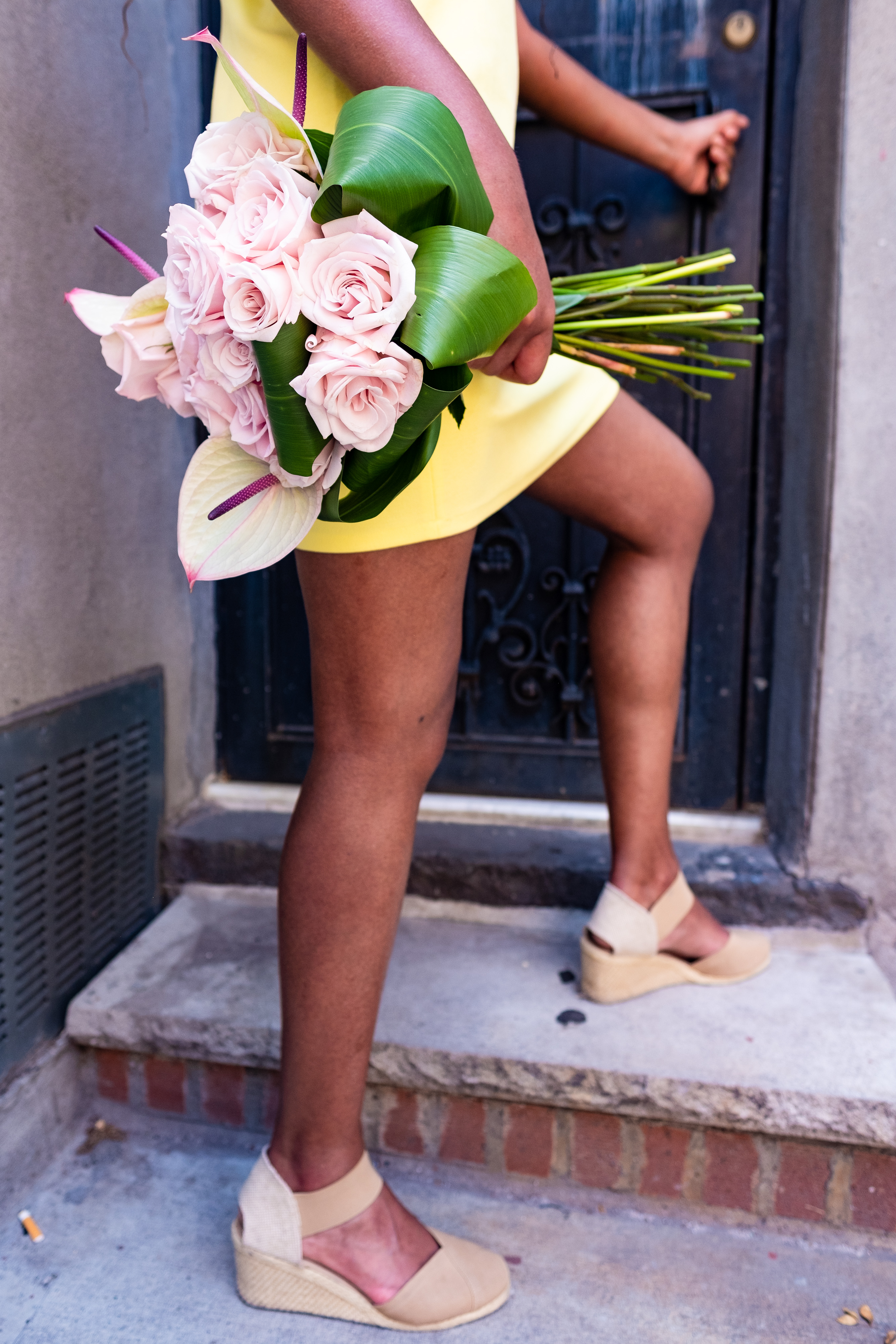 Woman wearing a yellow dress and holding a bouquet of pink roses, against a black, rod iron door at Cassava House.