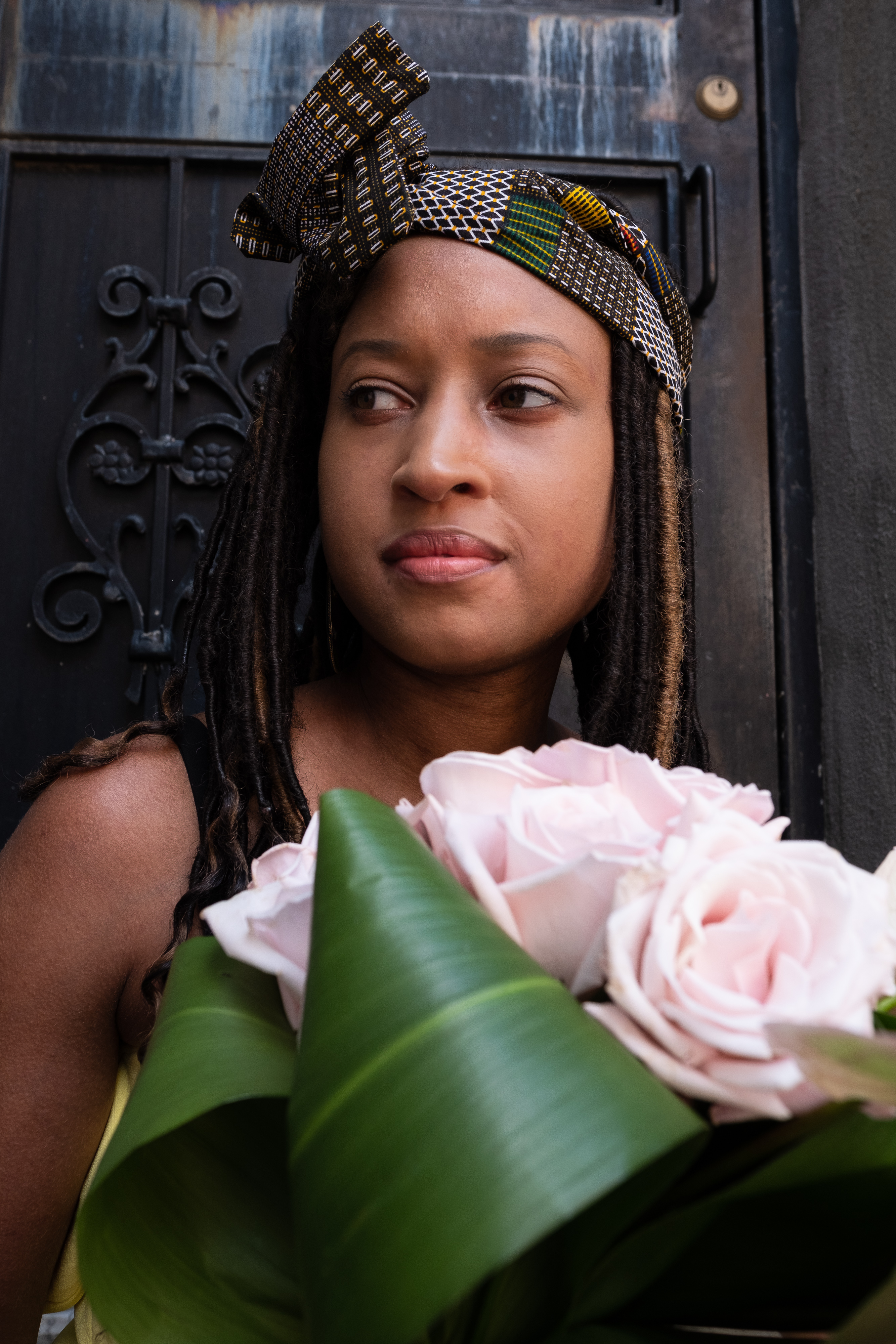 Beautiful woman wearing a brown headwrap with blocks of color throughout, against a black rod iron door at Cassava House. Holding a bouquet of pink roses.