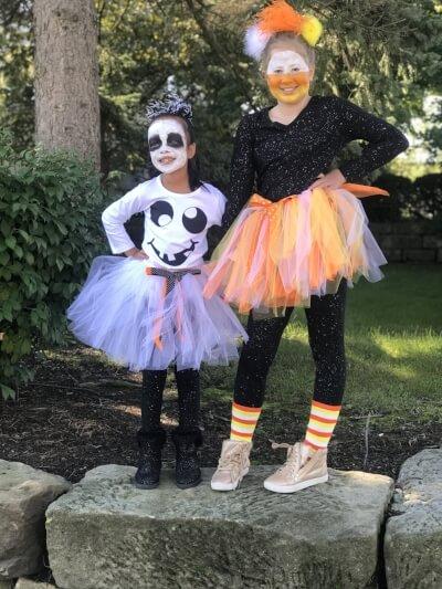 School kids wearing colorful Halloween tutus and makeup.