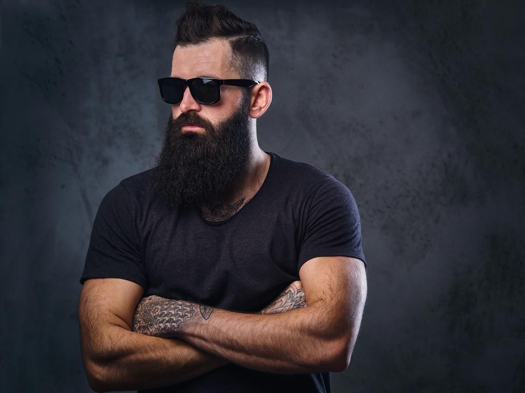 A bearded man with black sunglasses and arms crossed