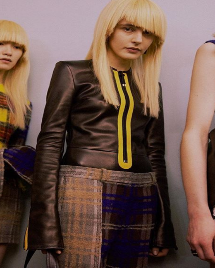 female model with blonde hair wearing fitted black louis vuitton leather jacket with yellow detail