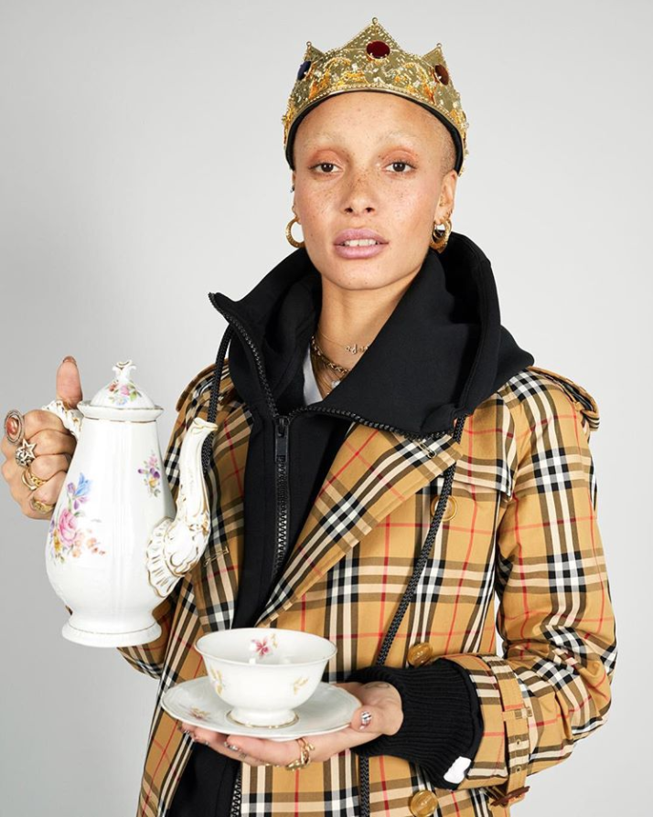 Adwoa Aboa wearing a brown chequered Burberry coat holding a cup of tea
