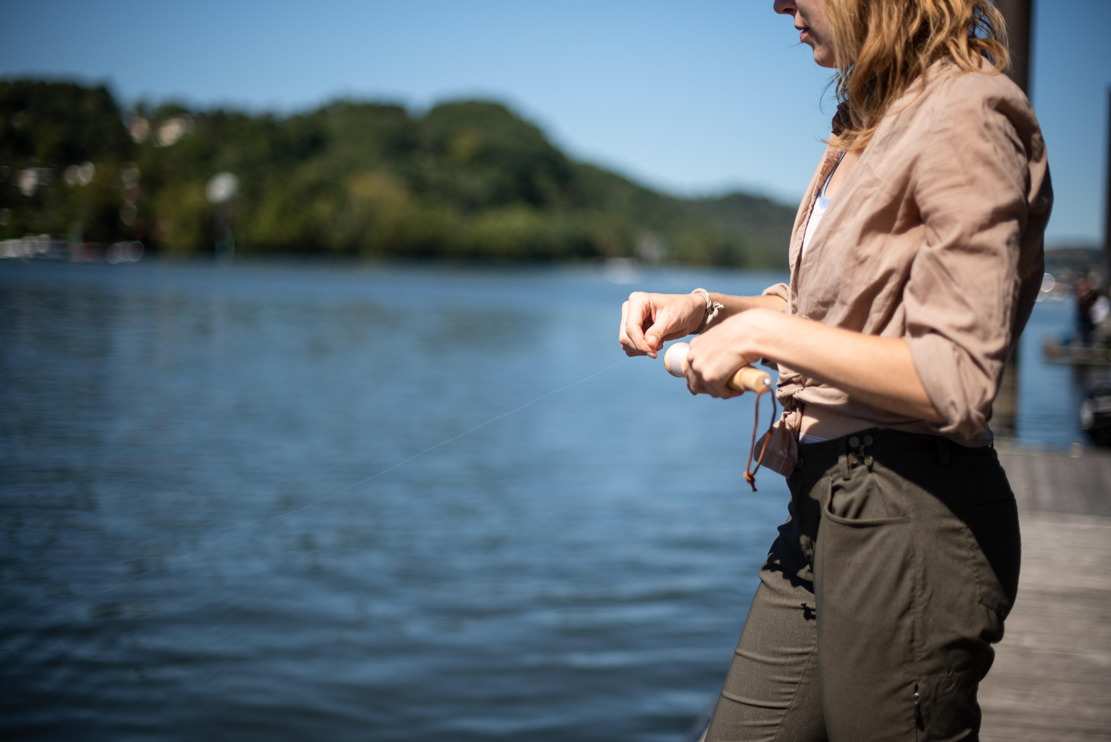A woman reeling in the Daggerfish portable fishing rod