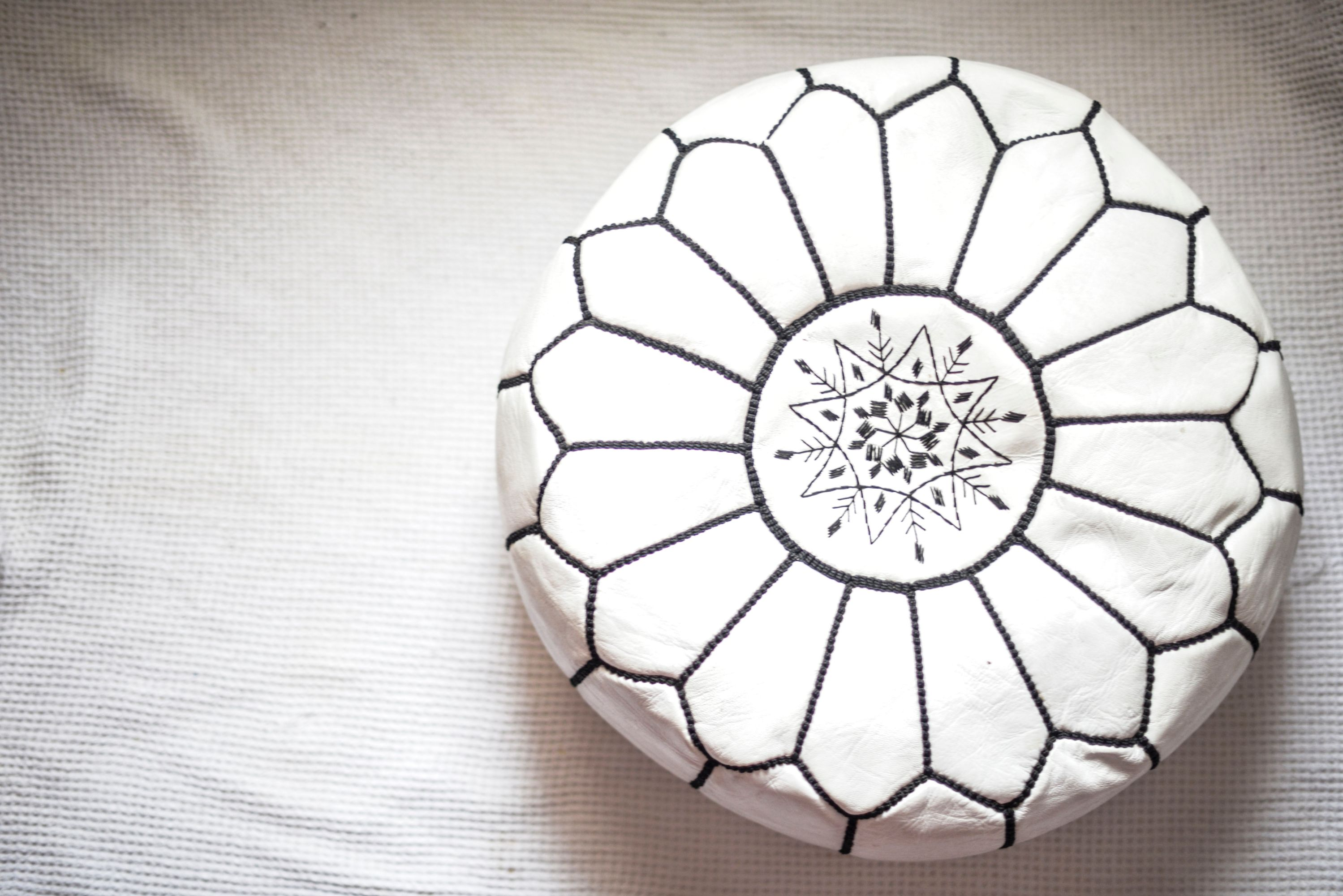 White and Black Moroccan leather pouf on white backround