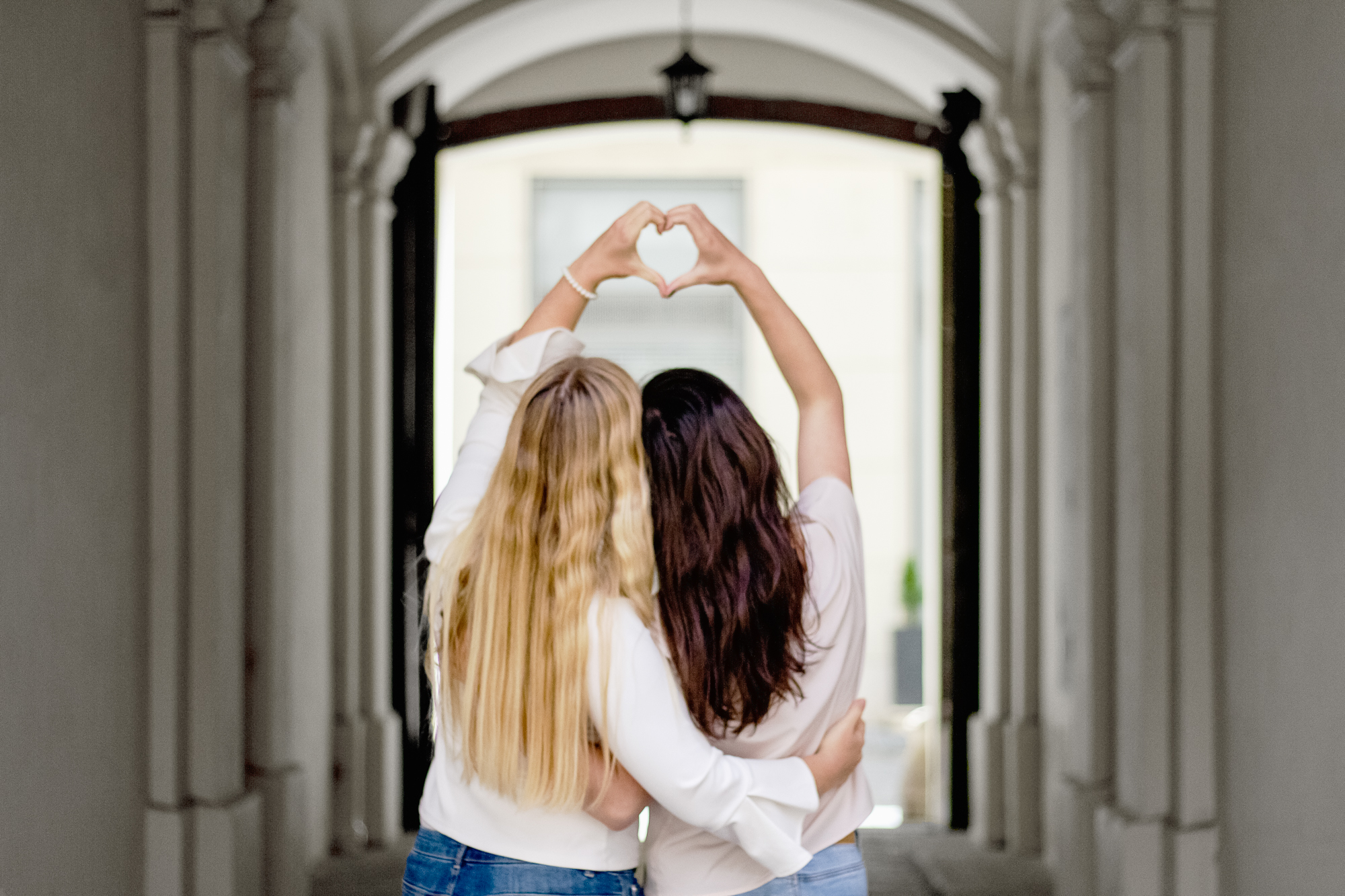 two women hugging, women supporting women, women forming hearts with their hands, blonde and brunette women
