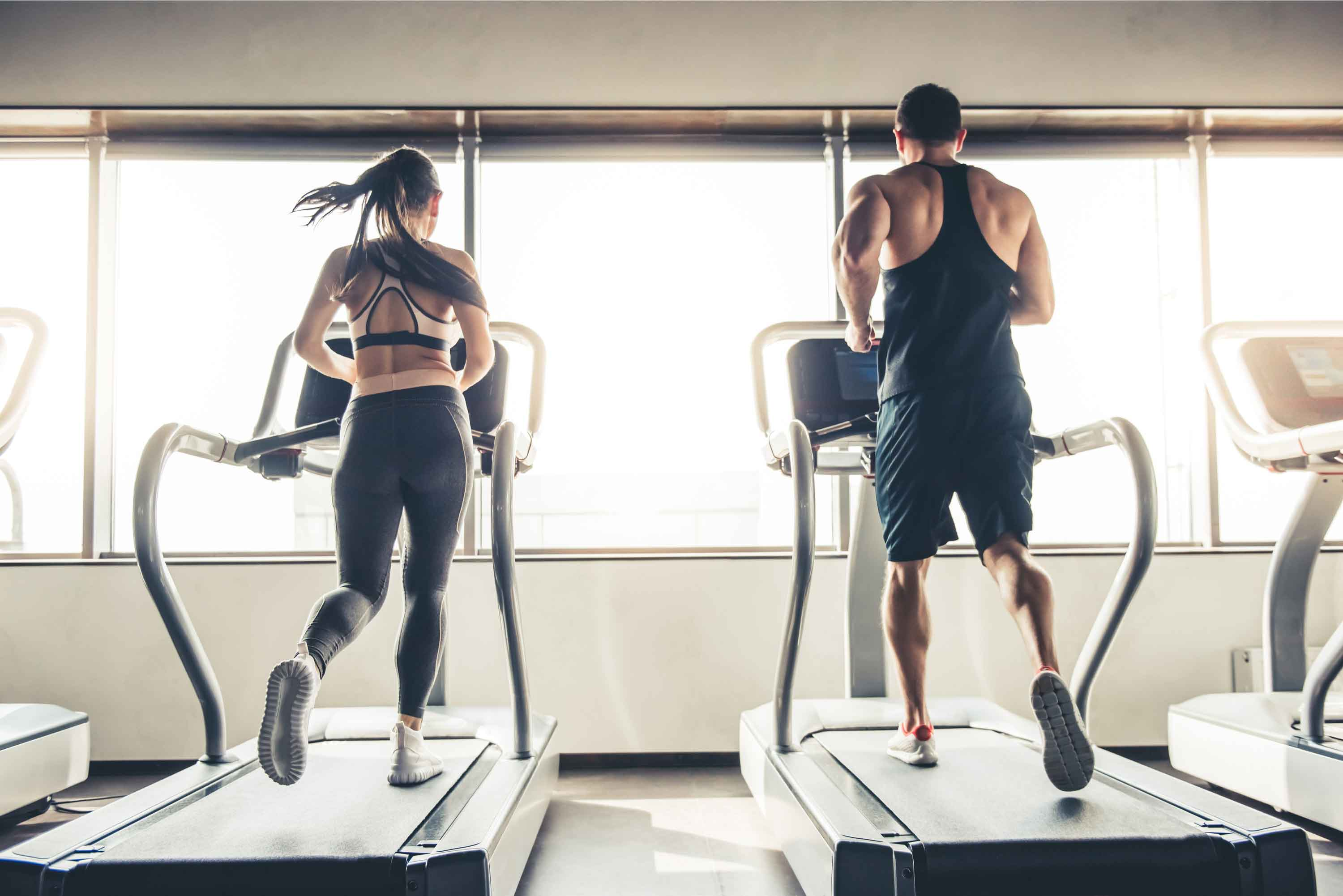 Couple on Treadmill Working Out Together