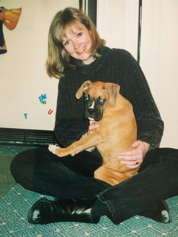 Woman with boxer puppy in her lap