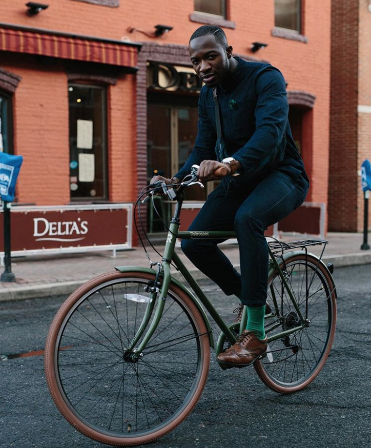 cyclist riding a critical mens green bike